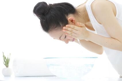 化粧水パックの前に洗顔する女性