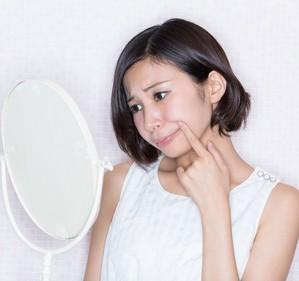 たるみを鏡でチェックする女性