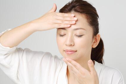 手で化粧水をつける時のポイントを考えながら実践する女性
