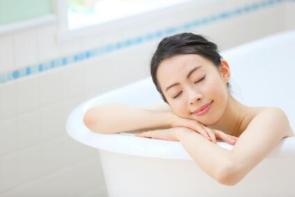 お風呂で身体を温めてむくみ対策を行う女性