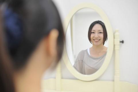 鏡で笑顔をチェックする女性