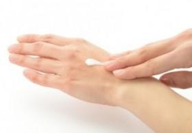 手にハンドクリームを塗っている女性