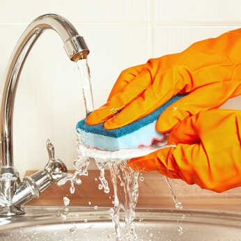 Hands in rubber gloves wash the dirty plate under running water in the kitchen