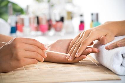 爪にマニキュアをする女性