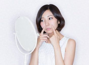 顔のたるみについて考える女性