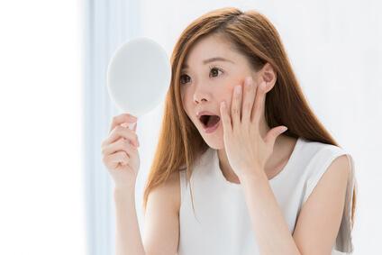 鏡で表情チェックをする女性