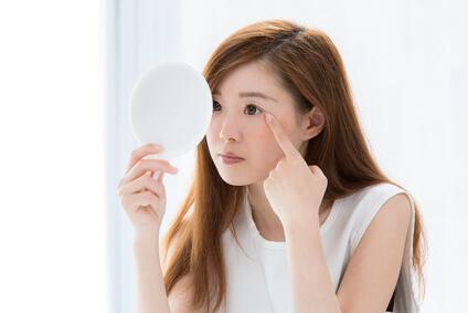 目の下のたるみの解消法を考える女性
