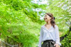 春の新緑の中を歩く女性