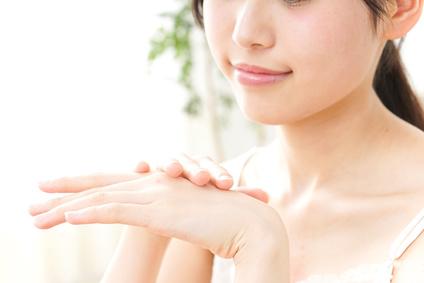 デコルテのケアと手肌のしわ対策を行う女性