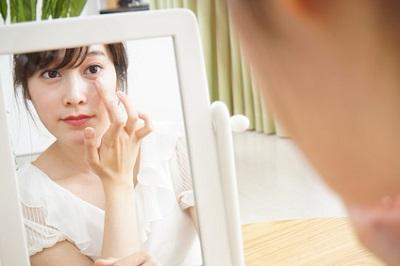 アイケア製品で目のケアをする女性