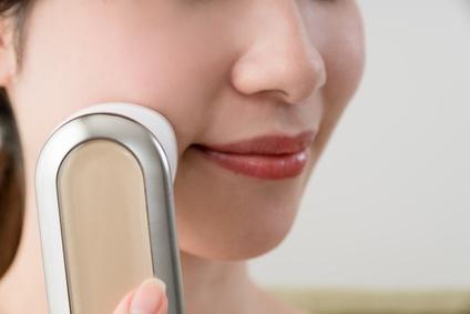 美顔器を使ってマリオネットラインを改善する女性