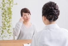 まつ毛貧毛症で病院の医師のアドバイスを受ける女性