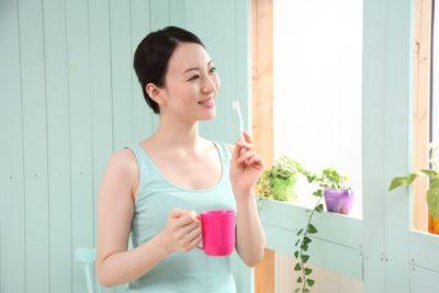 歯ブラシを使ってほうれい線ケアを行う女性