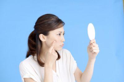 夏に鏡を見て自身の肌のくすみを気にする女性