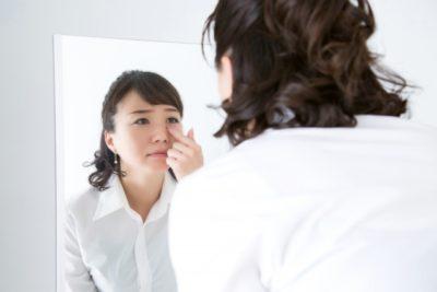 アレルギー性結膜炎になり鏡で目の状態を確認する女性