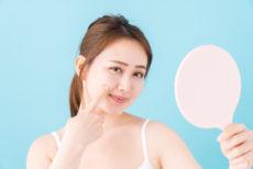 鏡で自身の肌の状態を確認する女性